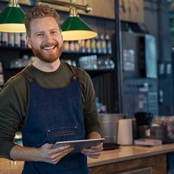 Successful small business owner using digital tablet and looking at camera. Happy smiling waiter wearing apron and holding digital tablet ready to take order. Portrait of young entrepreneur of coffee shop standing at counter with copy space.