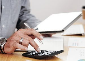 Close-up of businessman counting the profit of the company and using digital tablet at office desk
